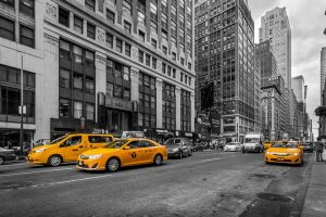 New York yellow taxis in a black and white scene