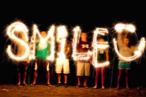 A group of people waving sparklers in the air to paint with light in a photograph